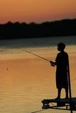 Visserij op het Meer bij Zonsondergang stock afbeelding