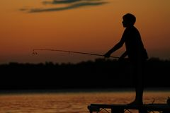 Visserij op het Meer bij Zonsondergang royalty-vrije stock afbeeldingen