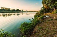 Visserij op het meer bij zonsopgang stock afbeelding