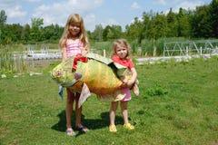 Visserij op het meer Twee leuke blonde Kaukasische meisjes houdt een grote muffe stuk speelgoed vis Royalty-vrije Stock Afbeeldingen