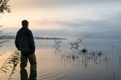 Visserijavonturen, karper visserij Vroege ochtend met mist en visser met hoge rubberlaarzen Royalty-vrije Stock Afbeeldingen