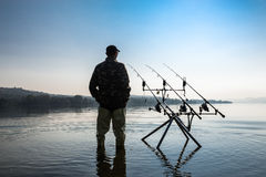 Visserijavonturen Visser die een vis met karper visserijtechniek wachten te vangen Stock Afbeeldingen