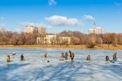 Vissers die en op ijs zitten lopen stock fotografie