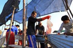 Vissers die kwallenvangst van overzees verwerken Stock Afbeeldingen