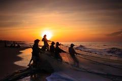 Vissers die netten bij zonsopgang slepen Stock Foto's