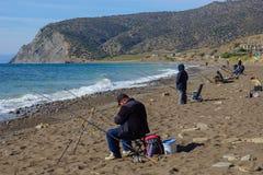 Vissers die op het strandberoep vissen voor mensen stock foto