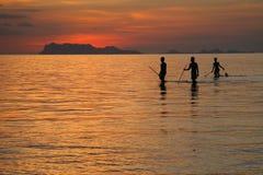 Vissers die tegen zonsondergang silhouetteren Stock Foto
