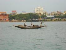 Vissers die vissen vangen door houten boot stock fotografie