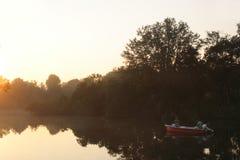 Vissers op meer tijdens zonsopgang Stock Foto