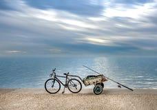 Vissers` s fiets met aanhangwagen op strandboulevard onder dramatische sk royalty-vrije stock foto