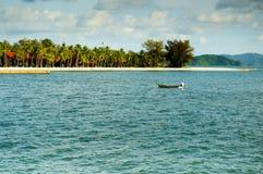 Vissersboot alleen in de baai met blauw water en bos Royalty-vrije Stock Afbeeldingen