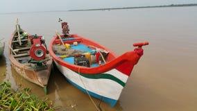 Vissersboot dichtbij de rivierbanken die wordt verankerd stock foto