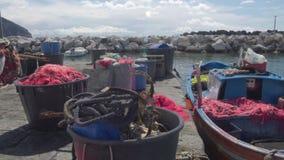 Vissersboot dichtbij pijler wordt geparkeerd, drijfnetten die in manden, kleine onderneming liggen die stock videobeelden