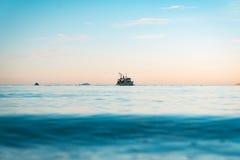 Vissersboot die bij zonsondergang terugkeren Stock Afbeeldingen