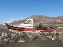 Vissersboot die op droog land in het dessert is vastgelopen Stock Foto's
