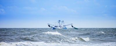 Vissersboot die in ruwe overzees vissen Stock Afbeeldingen