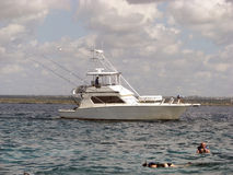 Vissersboot en snorkelend op het koraalrif Stock Afbeelding
