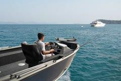 Vissersboot en visser in oceaan stock foto's