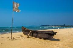 Vissersboot en witte vlag op zandig strand bij Arabische overzees India Royalty-vrije Stock Afbeeldingen