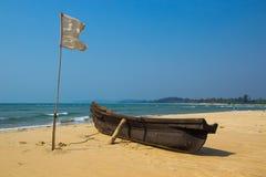 Vissersboot en witte vlag op zandig strand bij Arabische overzees India Stock Afbeeldingen