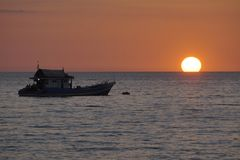 Vissersboot en zonsondergang stock foto's