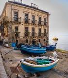 Vissersboot op de bestrating voor de oude bouw in klein dorp in Calabrië, Scilla, Italië stock afbeelding