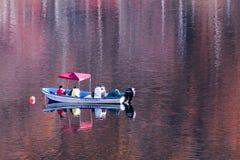 Vissersboot op de herfstmeer stock afbeelding