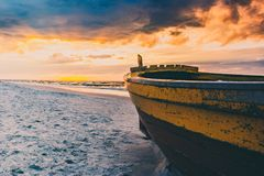 Vissersboot op het strand tijdens zonsondergang stock foto's