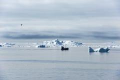 Vissersboot tussen Ijsbergen, Groenland stock foto