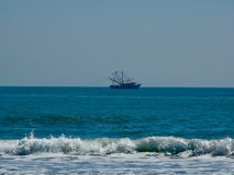 Vissersboot voor de kust stock foto's
