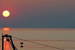 Vissersboot in zonsondergang op de horizon boven overzees Stock Afbeeldingen