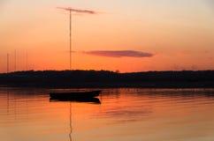 Vissersboten één in baai tijdens een kleurrijke oranje zonsondergang Stock Foto's