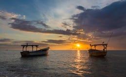 Vissersboten en gouden zonsondergang over het overzees Stock Afbeelding