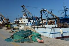 Vissersboten en netten in Trani, Apulia, Italië Mening van de oude haven Stock Foto's