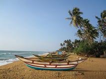 Vissersboten op een zandig strand met palmen stock afbeeldingen