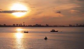 Vissersboten op het overzees met stadsmening in zonsopgangtijd royalty-vrije stock foto