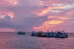 Vissersboten op zee onder een rode en oranje zonsondergang Royalty-vrije Stock Afbeelding