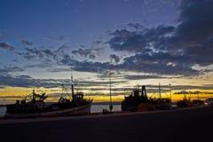 Vissersboten tegen zonsondergang worden gesilhouetteerd die stock afbeelding