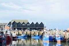 Vissersboten in Whitstable-Haven met rij van pakhuizen op achtergrond Stock Foto's