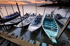 Vissersdokken die op water bij zonsondergang drijven stock afbeeldingen