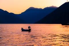 Visserssilhouet bij zonsondergang op bergachtergrond in Kotor-Baai Montenegro Stock Fotografie
