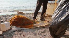Vissersstapel op visnet bij zandig strand stock videobeelden