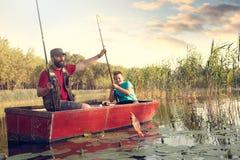 vissersvader die zijn zoon helpen om hun eerste vangst te trekken royalty-vrije stock fotografie