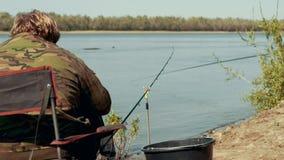 Visserszitting die op stoel door rivier bijna hengel op beet achtermening wachten stock video