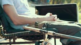 Visserszitting die op stoel door rivier bijna hengel op beet bij de zomerdag wachten stock videobeelden