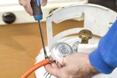 Vissez la bande de fixage au tuyau en caoutchouc du réducteur de cylindre de gaz Photographie stock libre de droits