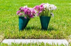 Vissnade blommor på en allvarlig markör i en veterankyrkogård Royaltyfri Foto