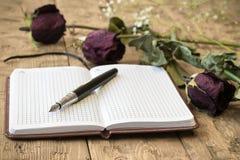 Vissnade rosor med en anteckningsbok och en reservoarpenna på en lantlig tabell Arkivbild