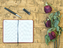 Vissnade rosor med en anteckningsbok och en reservoarpenna på en lantlig tabell Royaltyfri Fotografi