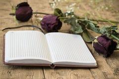 Vissnade rosor med en anteckningsbok och en reservoarpenna på en lantlig tabell Arkivfoto